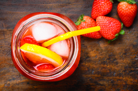 infused: Strawberry lemonade, beverage.Fruit infused water in mason jar on dark rustic wood background. Stock Photo