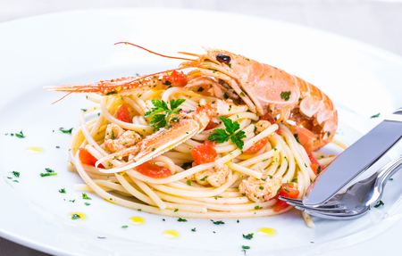 recipe background: Plate with seafood pasta.Italian restaurant plate menu, noodles with prawns, langoustines, lobster. Stock Photo