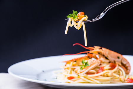 langoustine: Plate with seafood spaghetti pasta on fork.Italian restaurant plate menu, noodles with prawns, langoustines, lobster. Stock Photo