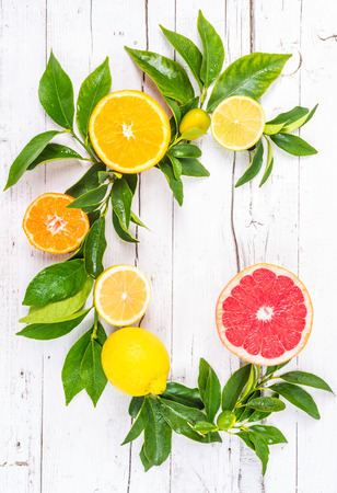 Fresh citrus fruits on white background wood. Vitamin C fruits letter.
