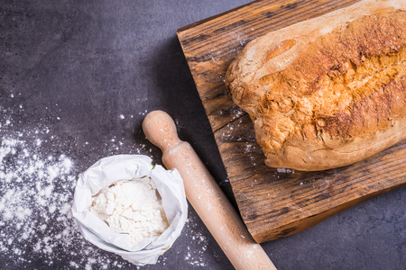 Fresh bread and flour top view on dark background copy space