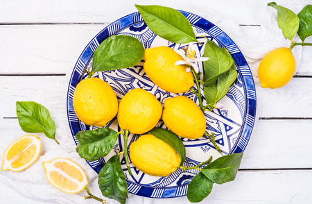 Fresh lemons in blue plate top view on white rustic wood background.