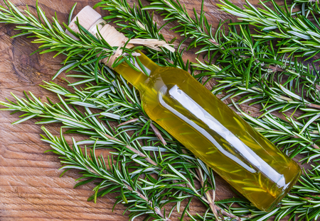 Fresh rosemary and oil infused with herbs top view on wood background. Stok Fotoğraf