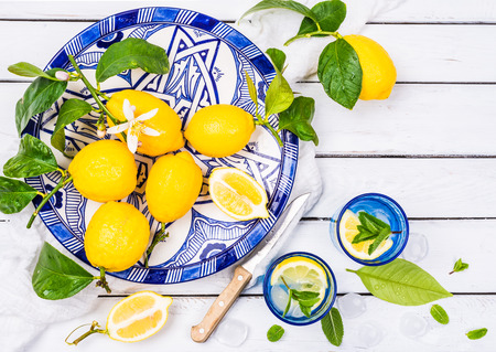 Lemons and water infused with lemon and mint on white background.