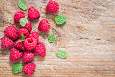 Raspberry on rustic wood background top view, copy space.