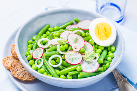 Salad bowl with pea and radish, eggs. Spring healthy vegetables plate. Stok Fotoğraf