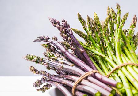 Fresh green asparagus and purple space.