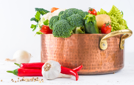 Vegetables broth or stock ingredients in copper pot on white wooden background.Healthy cooking, dieting, vegetables ingredients for soup or broth.