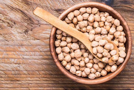 Dry chickpea in bowl top view on rustic wooden background.