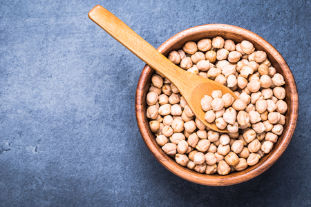 Dry chickpea in wooden bowl. Top view on dark background