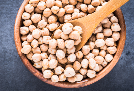 Dry chickpea in wooden bowl top view.