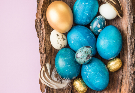 Easter naturally dyed eggs turquoise and gold on light pink background. Easter holiday background text space. Stok Fotoğraf