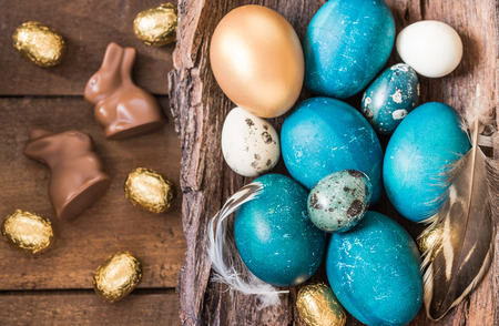 Easter eggs turquoise and gold on rustic wooden background. Easter holiday background text space.