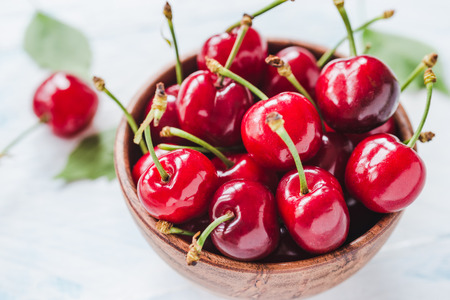 Cherry fruits in bowl on white wood background.