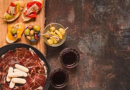 Spanish tapas with jamón ibérico or cured ham, olives, anchovies, wine. Gourmet appetizers copy space.