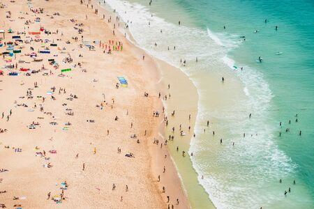 Panoramic view of ocean beach drone view. Beautiful long ocean beach with umbrellas and people.