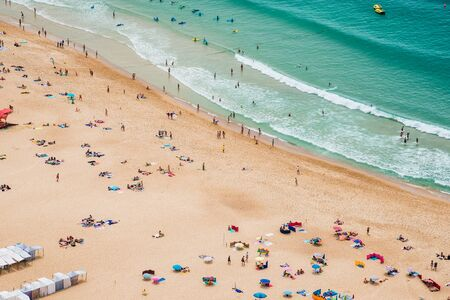 Panoramic view of ocean beach drone view. Beautiful long ocean beach with umbrellas and people. Stock Photo