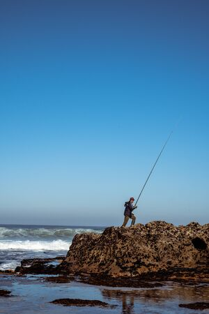 an old fisherman with a fishing rod on the Atlantic coast