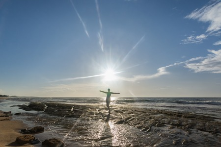 meditaion: Siloughette of a Woman Standing on the Rock in the Ocean in Hikkaduwa, Sri Lanka