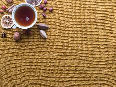 pili: Cup of black tea and dried fruit on woven yellow background