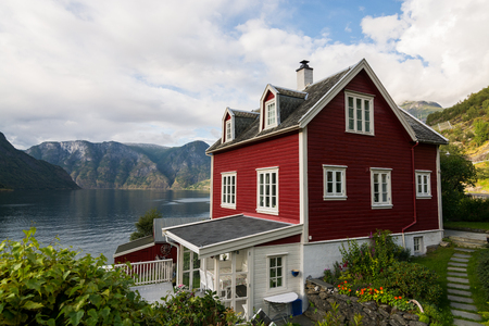 AURLAND, NORWAY - AUGUST 2017: Tradional red wooden house standing on the shore of Aurlandsfjord, Norway Editorial