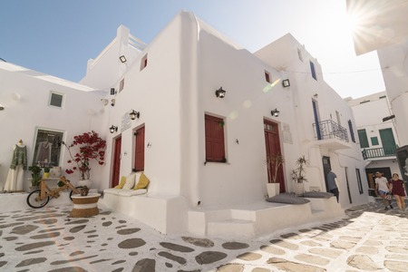 MYKONOS, GREECE - MAY 2018: The old street in Mykonos town district Little Venice with whitewashed house and street shop. Wide angle lens shot on a sunny day Editorial