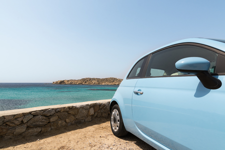 Light blue rental car parked next to the sea in Mykonos island, Greece 免版税图像