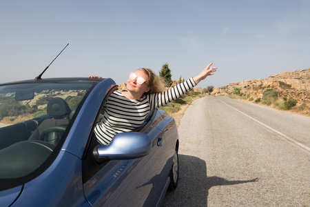 Young blonde woman driving convertible blue rental car without roof on mountain road in Naxos island, Greece