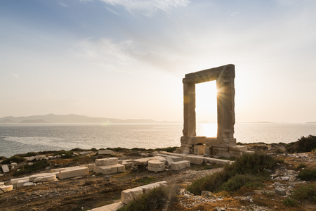 View over ruins of ancient marble doorway monument Portara at sunset in Naxos, Greece. Stock Photo
