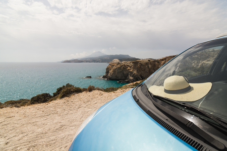 Blue car parked on sandy coast next to colourful rocks of Firiplaka beach on Milos island, Greece. Straw hat lying under the windshield