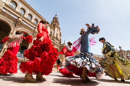 SEVILLE, SPAIN - MAY 2017: Young women dance flamenco on Plaza de Espana during famous Feria festival