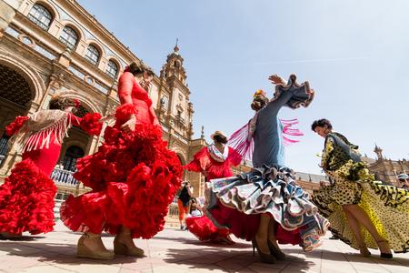 SEVILLA, ESPAÑA - MAYO DE 2017: Las mujeres jóvenes bailan flamenco en la Plaza de España durante el famoso festival de Feria