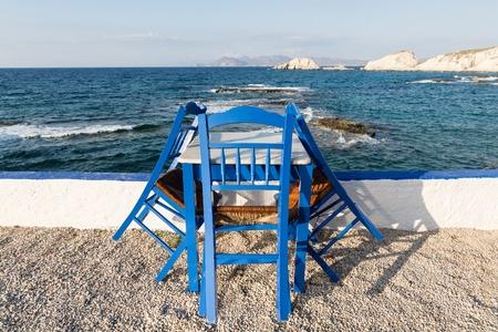 Table et chaises debout sur la côte de la mer Égée dans l'île grecque de Milos Banque d'images