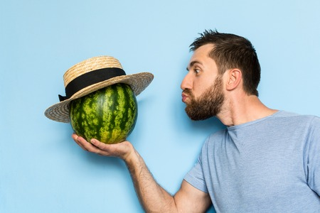 Young man holding and giving a kiss to a stripy watermelon in straw hat. Light blue background.
