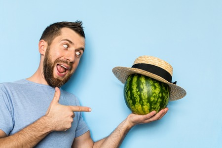 Young man holding a stripy watermelon covered with straw hat in front of his face. Light blue background, man showing hand shoot gun sign. Stock Photo