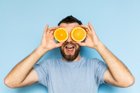 Young bearded and smiling man holding slices of orange in front of his eyes. Light blue background.