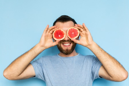 Young bearded and smiling man holding slices of grapefruit in front of his eyes. Light blue background. Stock fotó
