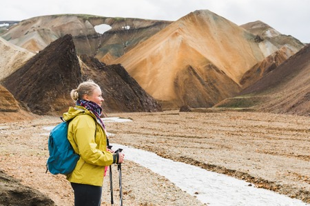 Woman hiking in the colourful mountains of Landmannalaugar national park, Iceland.