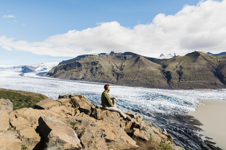 Man sitting on rocks overlooking Skaftafellsjokull part of Vatnajokull glacier in Skaftafell national park, Iceland.