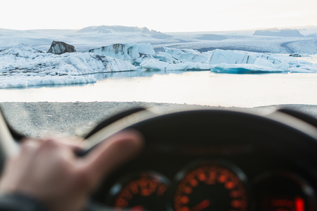 View from driver's seat over icebergs in Jokulsarlon lagoon at sunset, Iceland. Blurry foreground.