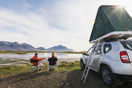 HOFN, ICELAND - AUGUST 2018: Young couple sitting in folding chairs next to offroad car with tent on the roof. Фото со стока