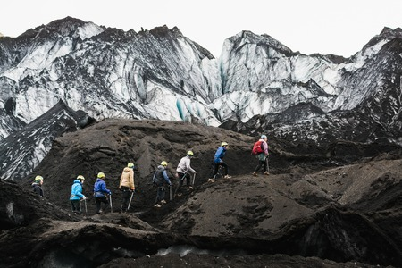MYRDALSJOKULL, ICELAND - AUGUST 2018: Group of tourists heading to the guided tour on Solheimajokull glacier, Iceland.