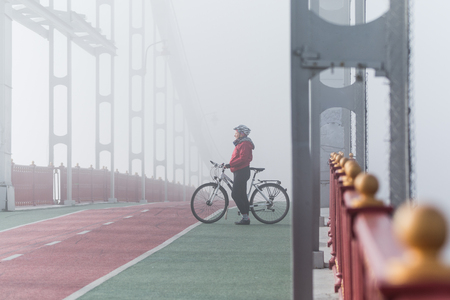 Woman in red jacket riding bicycle on a bridge in foggy morning, Kyiv, Ukraine.