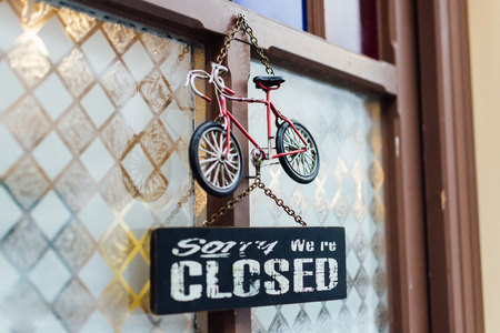 door chalk signboard saying Sorry we are closed with toy bicycle above