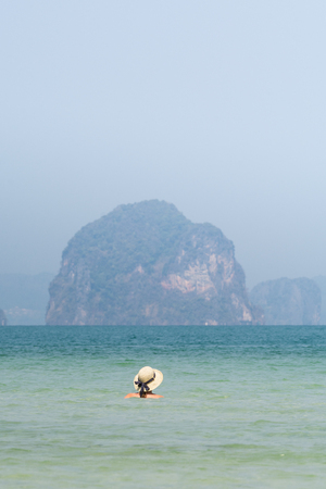Woman in straw hat swiming in the sea in Krabi Railey beach overlooking the harbour and mountains, Thailand. Vertical orientation