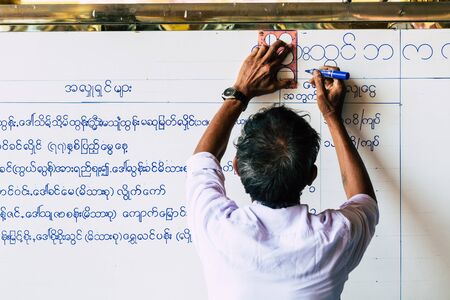 Yangon, Myanmar - March 2019: Burmese man writing temple ceremony schedule on the white board in Shwedagon stupa Editorial