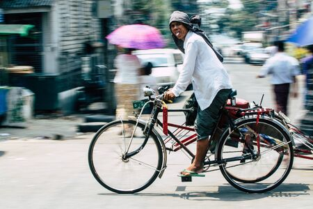 Yangon, Myanmar - March 2019: rickshaw man riding along the streets of Yangon. Редакционное