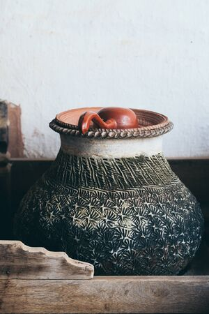 Traditional clay pot with drinking water and ladle in Myanmar Stock Photo