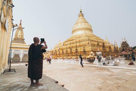 Bagan, Myanmar - March 2019: Burmese Buddhist monk taking picture of Shwezigon Paya golden temple