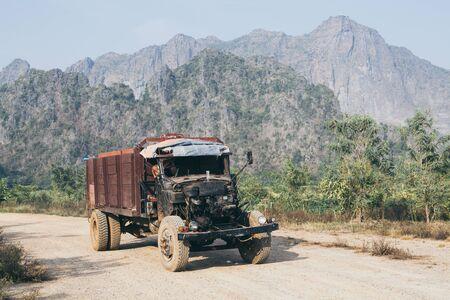 Alte LKW-Fahren auf der Schotterstraße mit Zwegabin-Berg im Hintergrund in Hpa-An, Myanmar. Standard-Bild